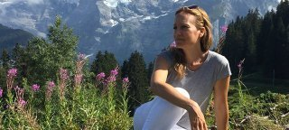 Amy Yuter sits on a hillside with mountains in the background