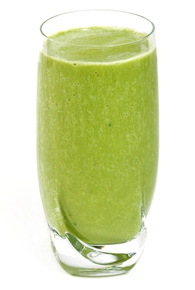 A glass of green smoothie on white background