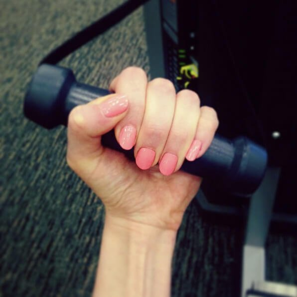 Closeup photograph of Jenny Lapan's left hand holding a dumbbell