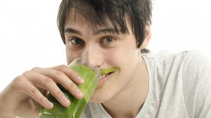 Man eating a green smoothie and wearing a smoothie mustache