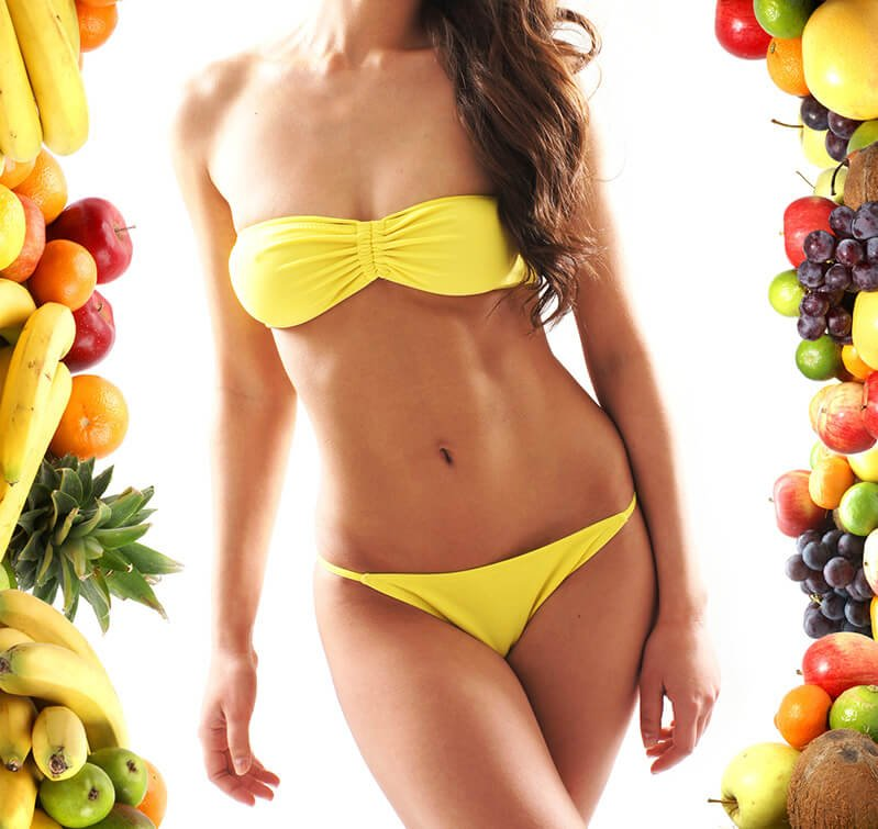 A woman in a yellow bikini is surrounded by fruits