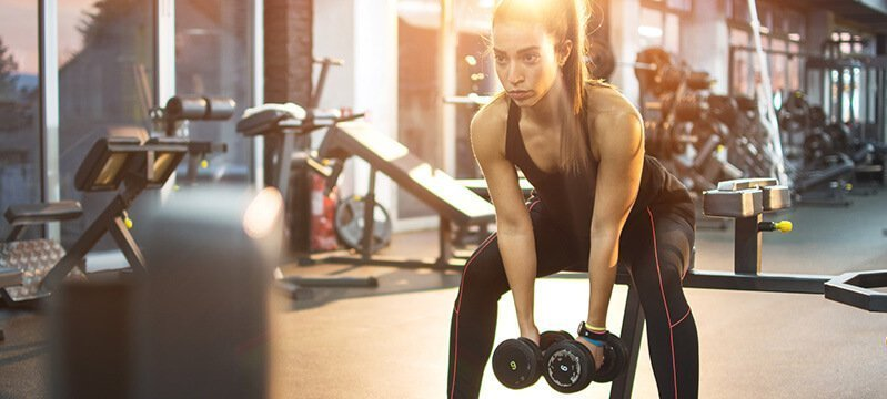 A woman lifts dumbbells in a gym