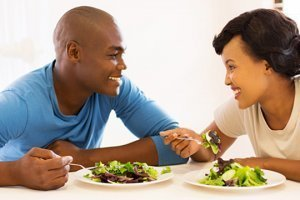 A man and woman eat salads at a table