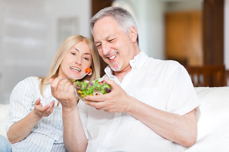 A man and woman eat salad on a couch