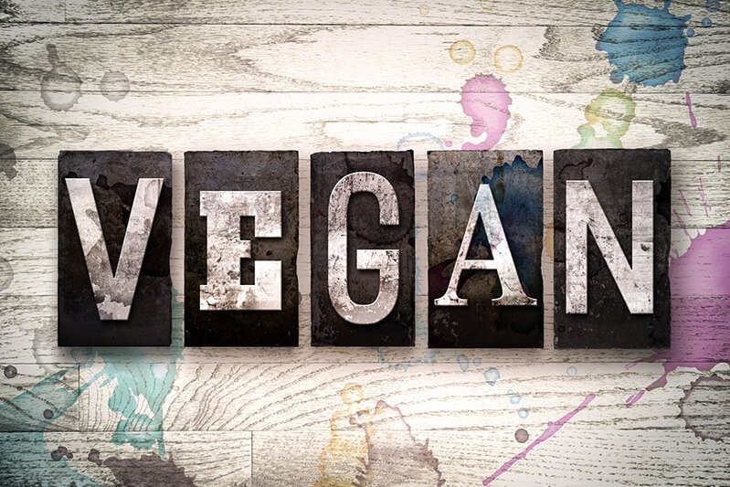 """Vegan"" in block letters on a painted wooden background"