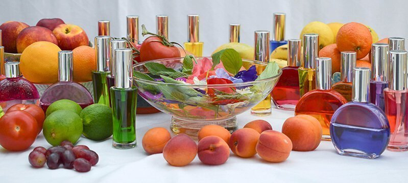 Colored oils and essences on display with fruits