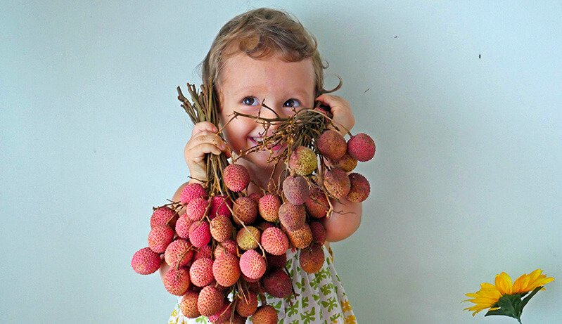 Elanie Tarbath holds lychees at 3 years old