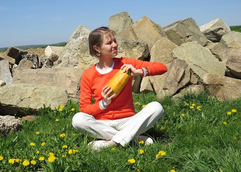 Eva Straub holds a papaya while sitting