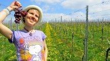 Eva Straub dangles grapes while posing in a field