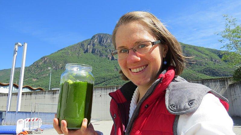 Eva Straub smiles while hoisting a green smoothie