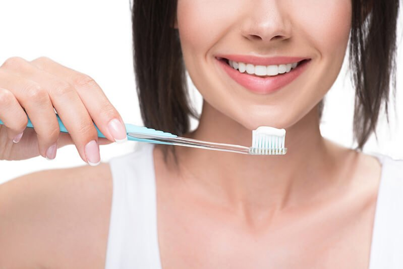 Woman holds a toothbrush topped with toothpaste, practicing oral hygiene care
