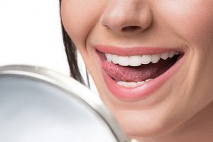 Woman running her tongue along her teeth while looking in a mirror 300x200 - Improving Oral Hygiene on a Raw Food Diet