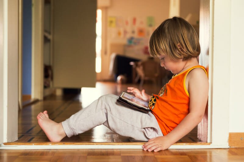Child plays with a tablet and leans against a wall, exhibiting poor posture