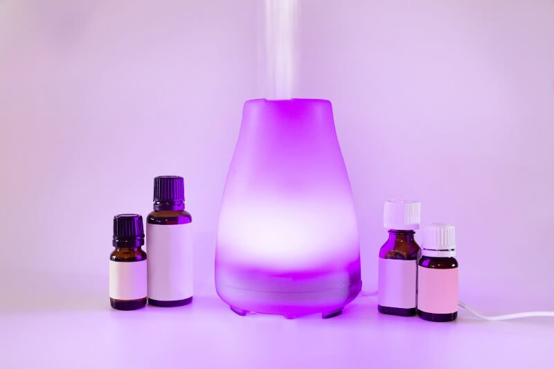 Essential oils and a diffuser lighted up purple