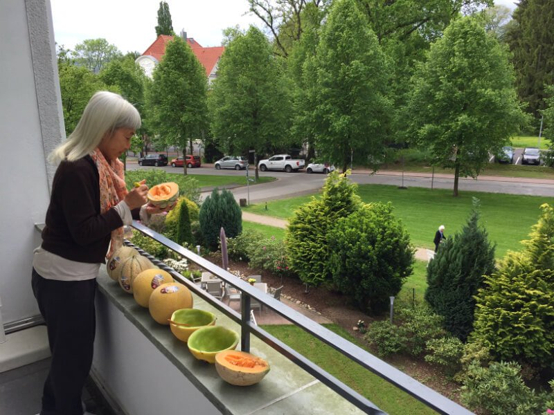 Ping Chan eats melons on a balcony in Germany