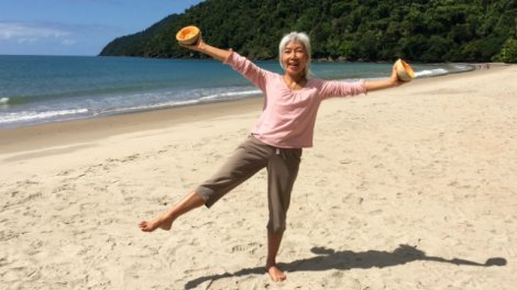 Ping Chan holds melon halves while standing on one leg on a beach