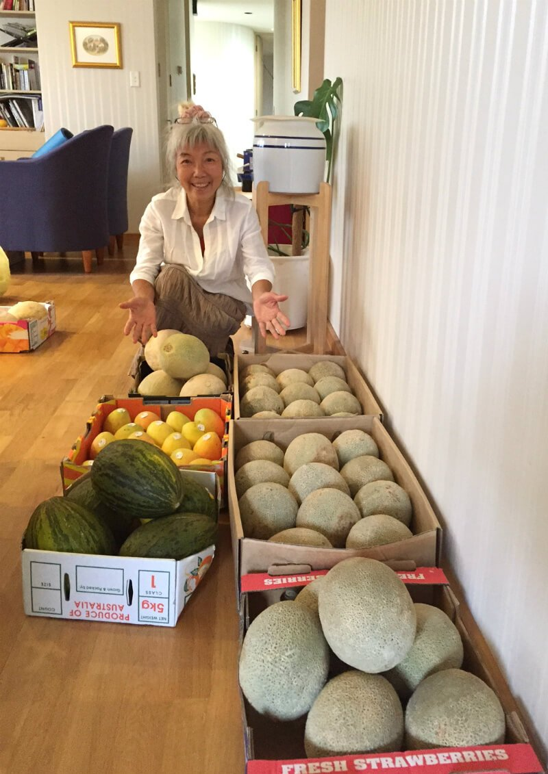 Ping Chan crouches beside dozens of melons