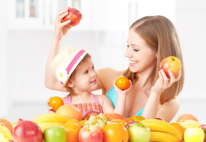 A mother and her daughter play with fruit