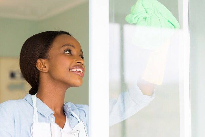 With essential oils in glass cleaner, a woman cleans her home windows