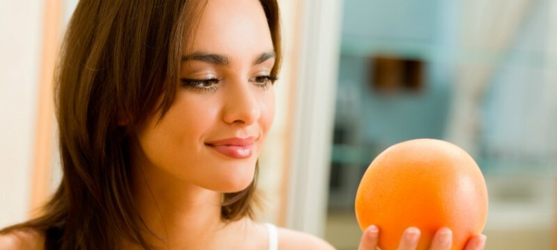 Woman gazes at a grapefruit she holds