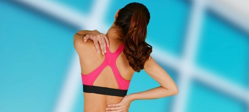 Woman holds her achy back and neck