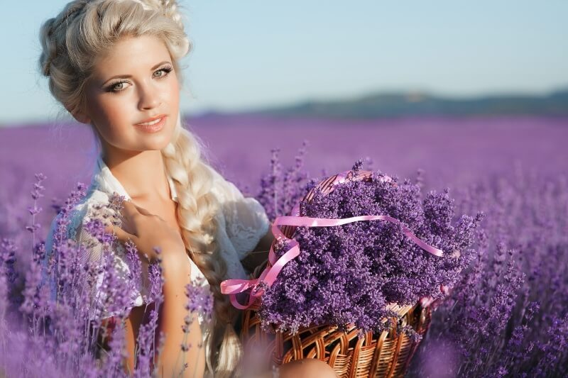 A blonde woman is photographed in a lavender field