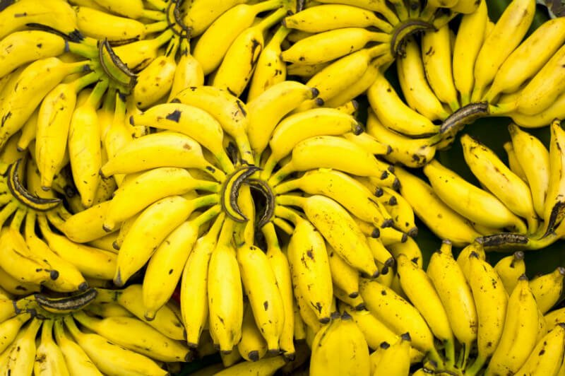 Many hands of bananas are stacked upon one another