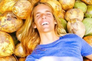 Nicolas Dudet lays on a bed of coconuts