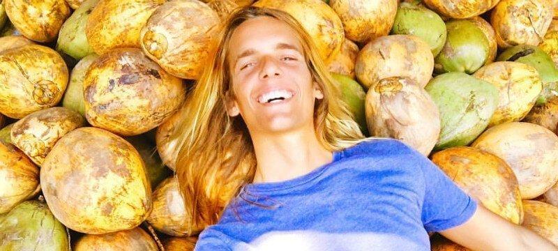 Nicolas Dudet lays on a bed of coconuts