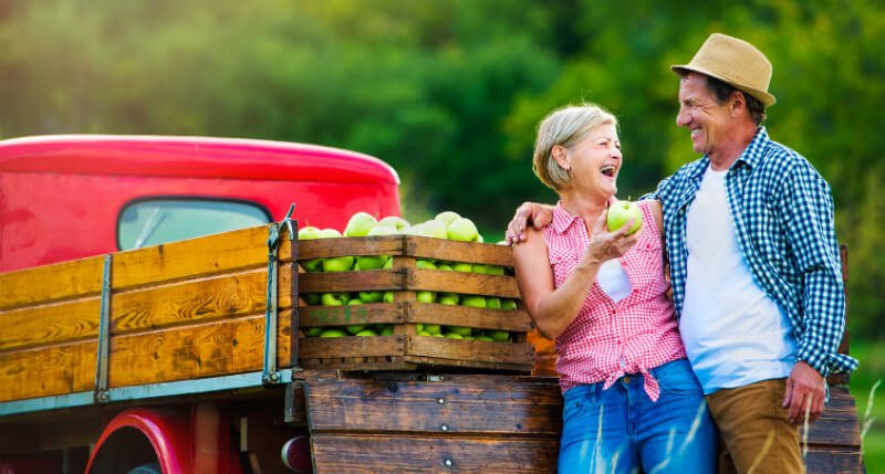 A woman enjoys freshly picked apples with a man beside a truck