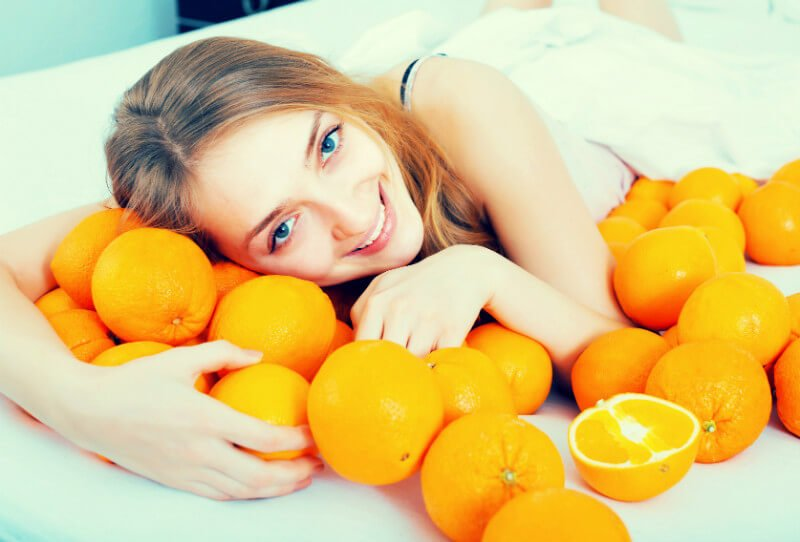 A young woman playfully curls up beside 20-plus oranges