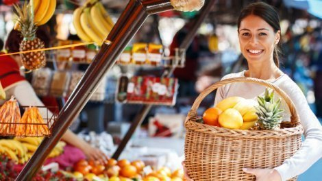 A young woman buys fruits at a stand