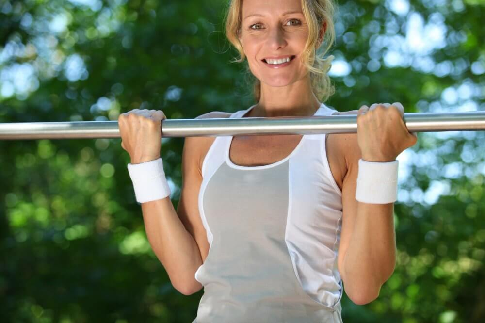 Exercise Guide - Posture Correction Exercises - Calisthenics - Peak Health - Woman Doing Chin-Ups Outside - Fruit-Powered