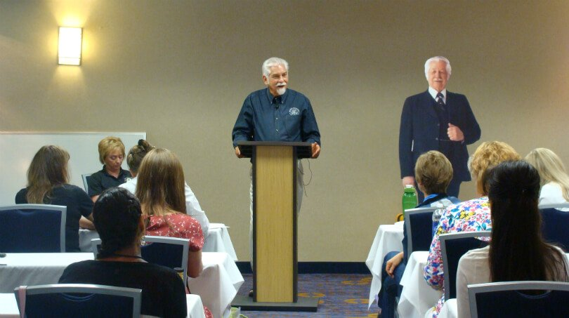 David Christopher lectures beside a Dr. John R. Christopher cardboard cutout