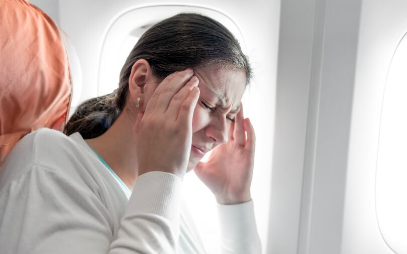 Woman with headache on plane - healthier jet-setting