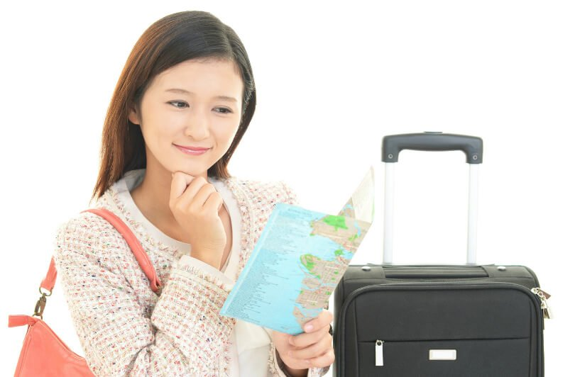 Woman with suitcase and map - healthier jet-setting - air travel health tips