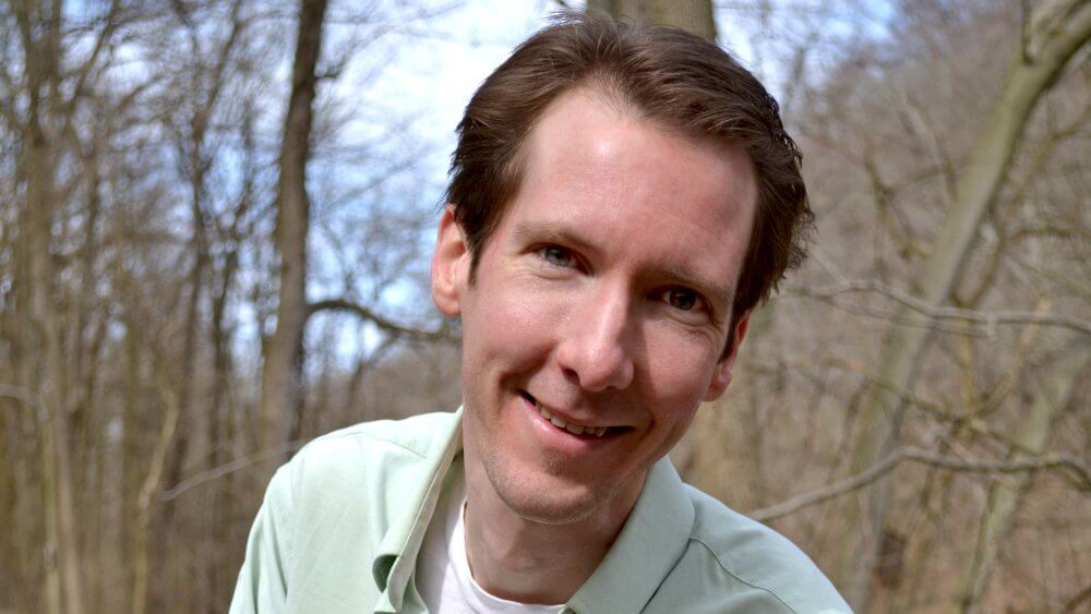 About Fruit-Powered: Brian Rossiter, a holistic health coach, standing in a wooded area- Fruit-Powered
