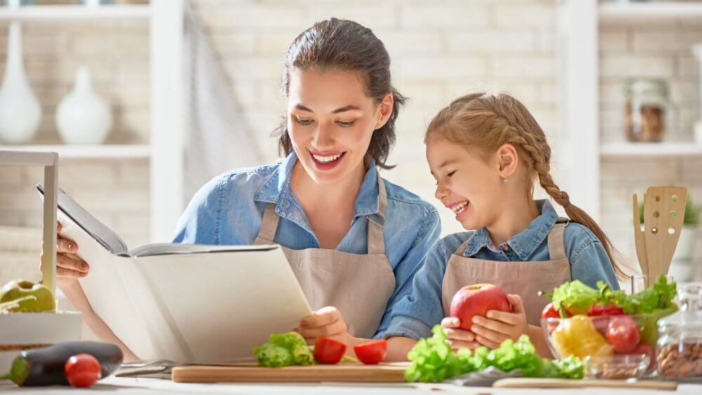Fruit diet - mother and daughter reading recipe book - Fruit-Powered