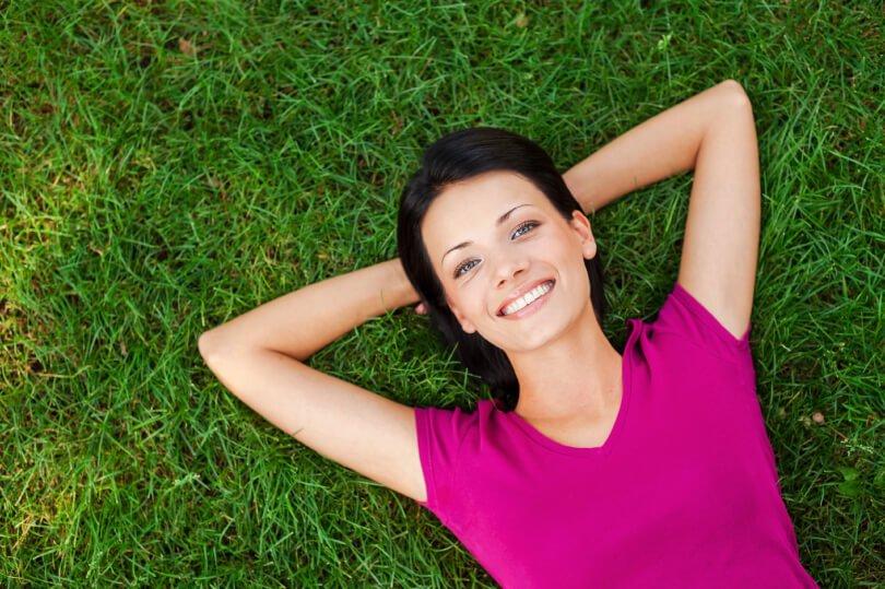 Neuro Emotional Technique - NET - woman relaxing on grass - Fruit-Powered