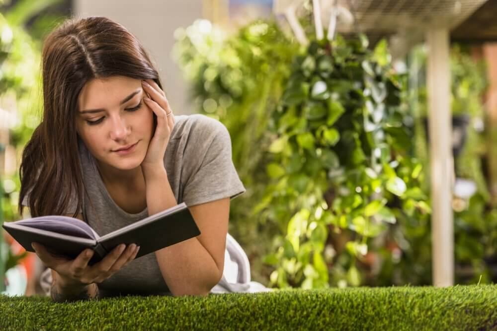 Woman reading book on grass - Fruit-Powered