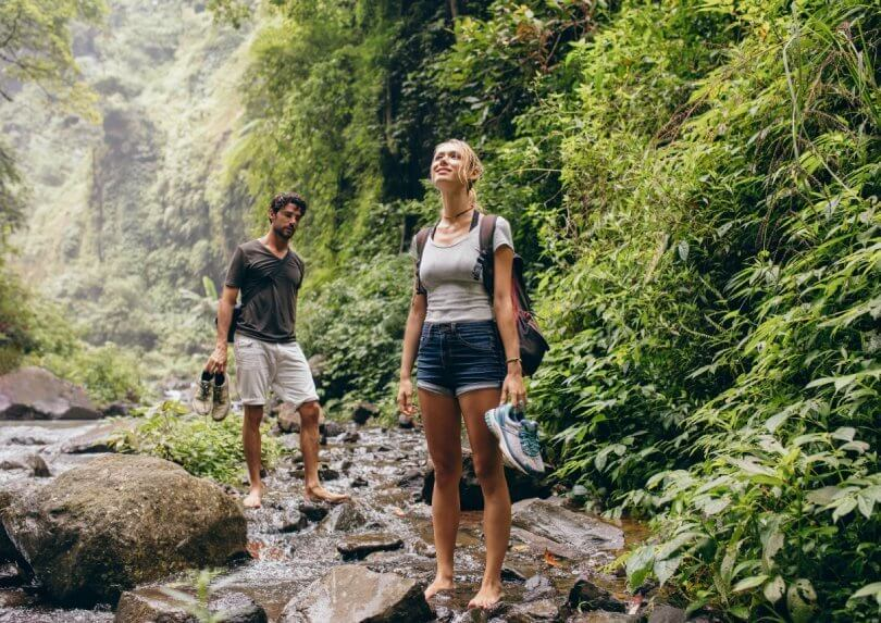 Forest bathing - enjoy beauty and health benefits of nature - man and woman hiking along creek - Fruit-Powered