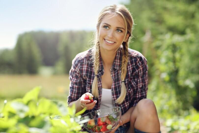 Forest bathing - enjoy the beauty and health benefits of nature - woman picking strawberries - Fruit-Powered