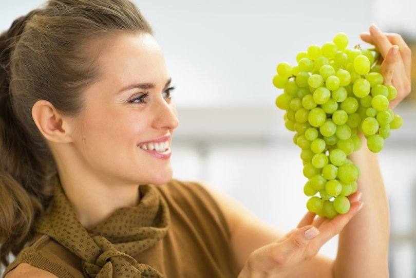 How to be successful on a raw vegan diet - woman looking at green grapes - Fruit-Powered