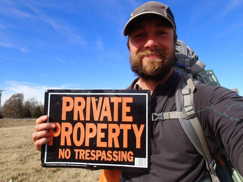 Ken Ilgunas holding private property sign - This Land Is Our Land - vandwelling - wanderlust - society - Fruit-Powered
