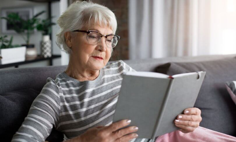 Proper sitting posture - elderly woman reading book on couch - Posture Exercises Method - Fruit-Powered