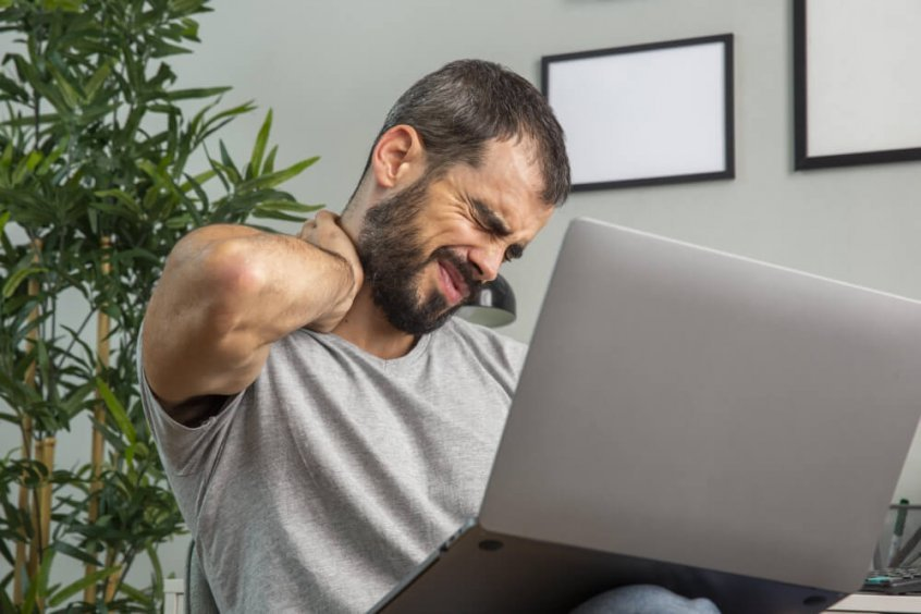 Computer neck - man reaching for neck - pain - laptop use - Fruit-Powered