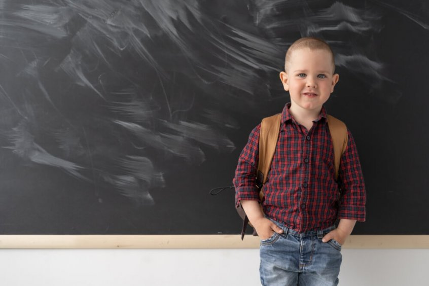 Forward head posture - schoolboy carrying backpack in classroom - Fruit-Powered
