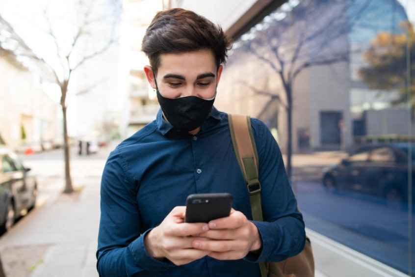 Man wearing COVID mask and on cell phone while walking in a city - Fruit-Powered