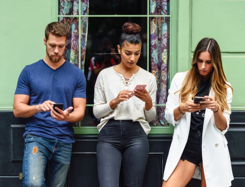 Tech neck - three adults look down using smartphones - Fruit-Powered