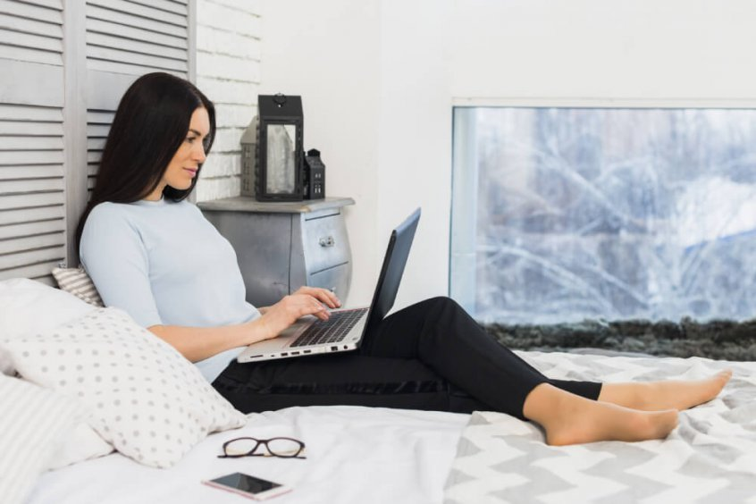 Tech neck - woman using laptop in bed - Fruit-Powered